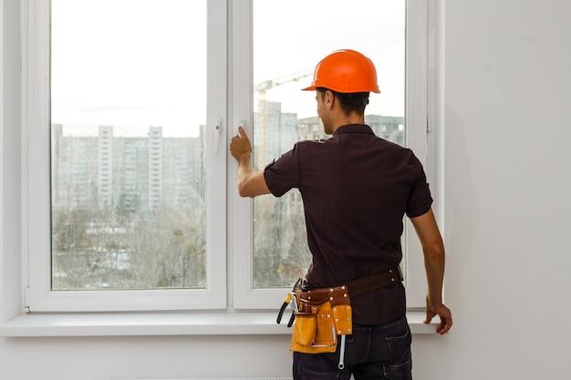 Stolarz naprawia ramy okienne, dom jest aktualizowany do sprzedaży