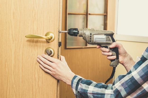 Stolarz naprawia zamek w drewnianych drzwiach, obracając śrubę wiertłem.
