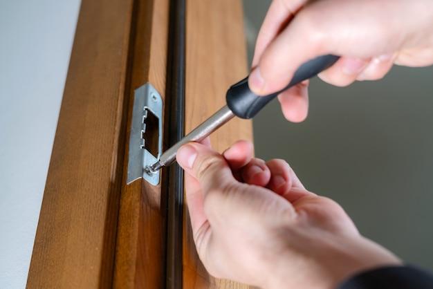 Stolarz naprawiający zamek drzwi, złota rączka dokręcający zawiasy drzwi.
