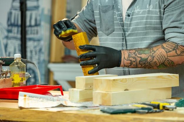 Stolarz pokrywa lakierem drewniany przedmiot