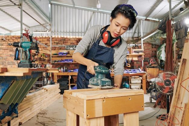 Stolarz polerujący powierzchnię drewnianą