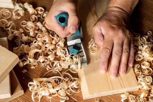 Stolarz pracuje na drewnie otoczonym trocinami