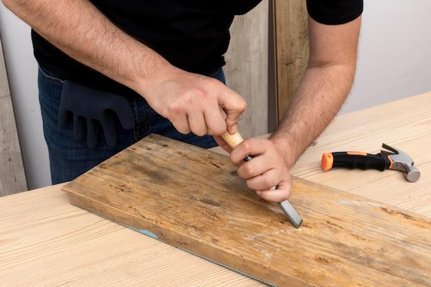 Stolarz pracuje na drewnie w swoim warsztacie