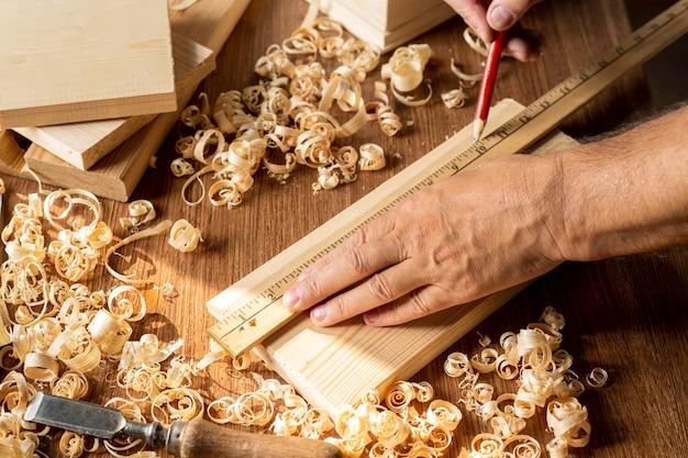 Stolarz pracuje na kawałku drewna ołówkiem