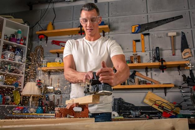 Stolarz pracuje przy obróbce drewna na obrabiarce. przecina detale mebli piłą tarczową