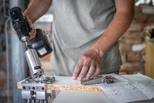 Stolarz pracuje z profesjonalnym, precyzyjnym narzędziem do wiercenia.