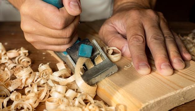 Stolarz pracuje z trocinami wytwarzającymi małą piłę