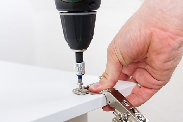Stolarz przykręca zawias do koncepcji usługi montażu mebli drzwiowych
