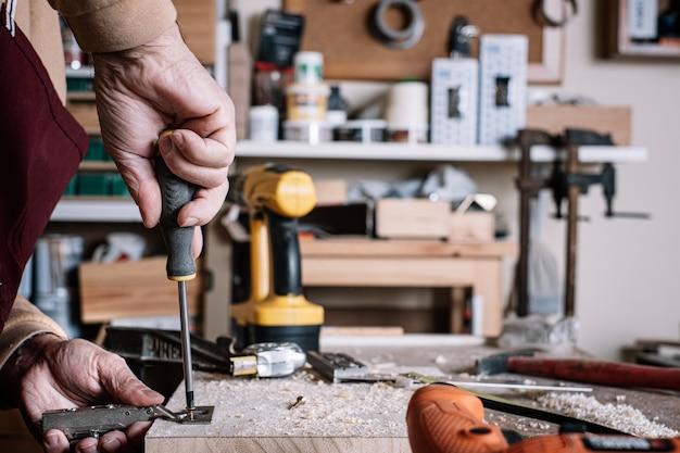 Stolarz przykręcając zawias do deski za pomocą śrubokręta