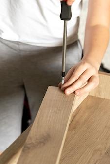 Stolarz przykręcił zawias do drewnianej deski, montując szafkę w domu