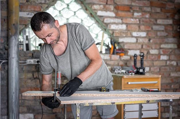 Stolarz robi prace drewniane za pomocą narzędzia ręcznego mocowania w swoim warsztacie.