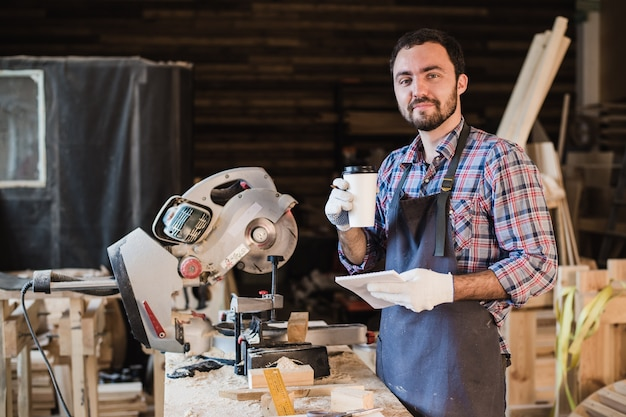 Stolarz robi sobie przerwę na kawę, trzymając notebook przed piłą tarczową w swoim warsztacie