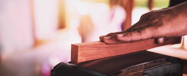 Stolarz szlifuje drewno papierem ściernym.