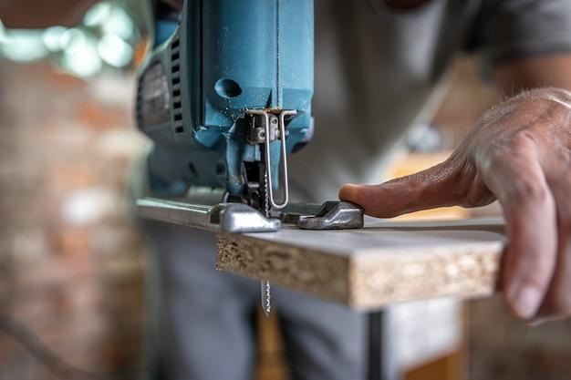 Stolarz tnie drewno za pomocą elektrycznej wyrzynarki, pracując z drzewem.