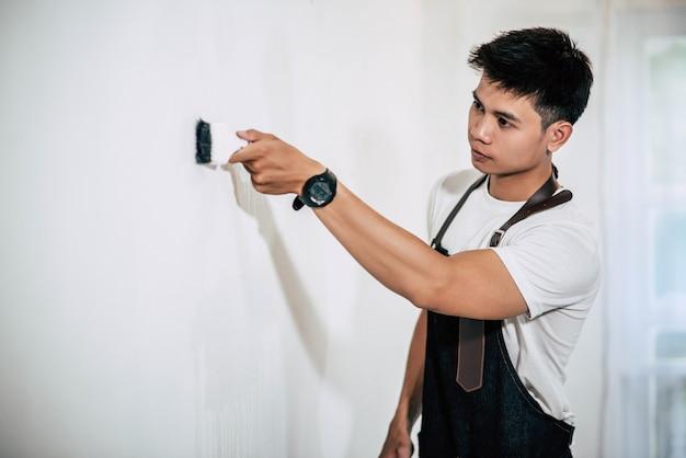 Stolarz trzyma pędzel i maluje drewno.