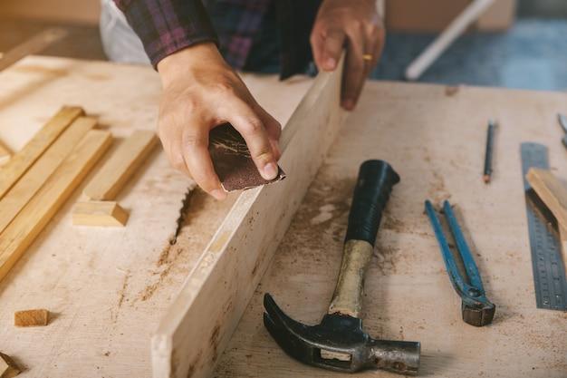 Stolarz używa papieru ściernego na drewnie. przemysł budowlany, prace domowe zrób to sam.