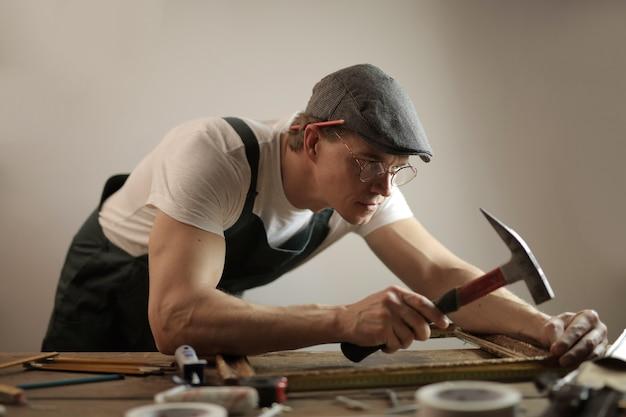 Stolarz w białym kasku, pracujący z młotkiem i śrubami, próbujący naprawić drewniany stół