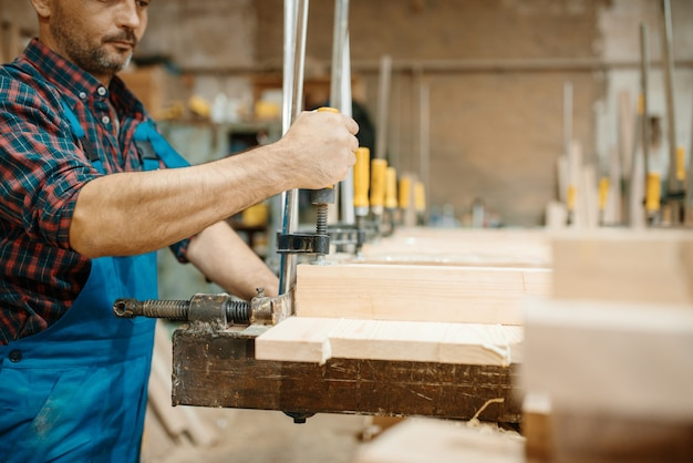 Stolarz w mundurze zaciska deskę w imadle, przy obróbce drewna, przemyśle drzewnym, stolarstwie. obróbka drewna w fabryce mebli, produkcja wyrobów z materiałów naturalnych
