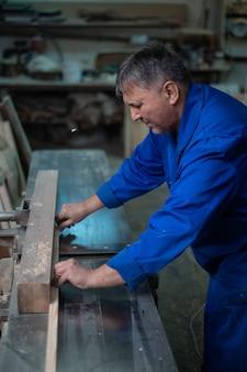 Stolarz w pracy w swoim warsztacie, obróbka drewna na maszynie do obróbki drewna