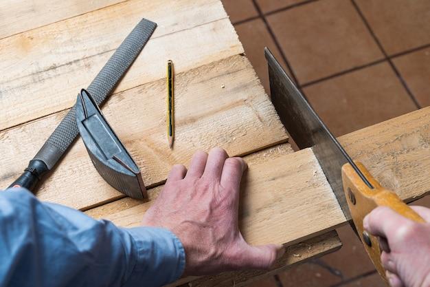 Stolarz w trakcie renowacji i wykonania drewnianego stołu