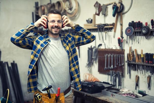 Stolarz w warsztacie zakładający ochraniacze na uszy i przygotowujący się do pracy