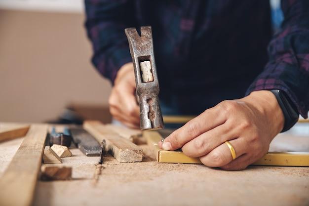 Stolarz wbija gwóźdź. przemysł budowlany, zrób to sam. drewniany stół roboczy.