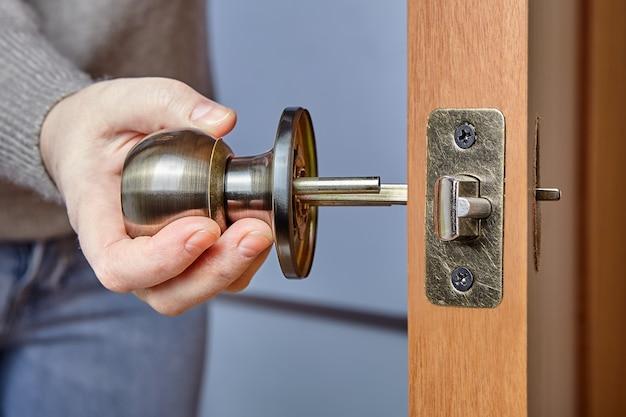 Stolarz wpycha trzpień klamki drzwi przez otwór czołowy i zespół zatrzasku.