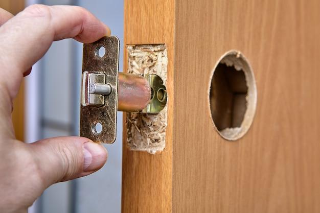 Stolarz wpycha zespół zapadki klamki drzwi przez otwór krawędziowy.