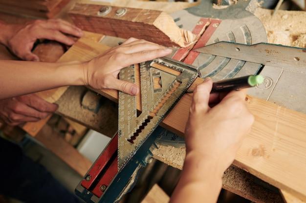 Stolarz wyznaczający drewniane deski