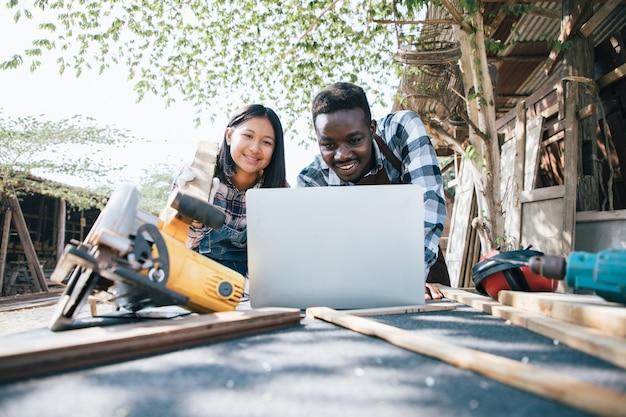 Stolarz z asystentem przy użyciu laptopa i narzędzi do drewna z własnego mieszkania w miejscu pracy