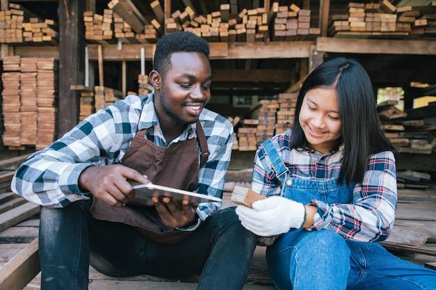 Stolarz z asystentem używający tabletu do wybierania drewna we własnym sklepie z drewnem