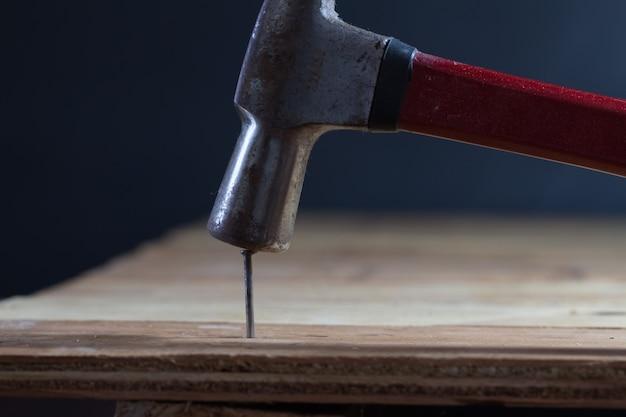 Stolarz za pomocą młotka uderza w gwóźdź na drewnianej podłodze