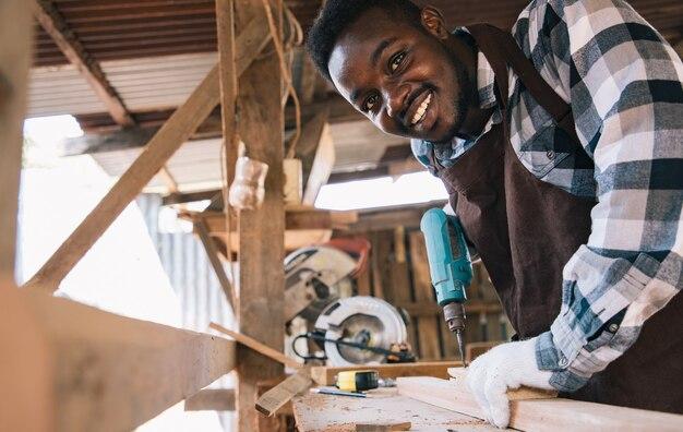 Stolarz za pomocą narzędzia wiertniczego do drewna własnego mieszkania w miejscu pracy