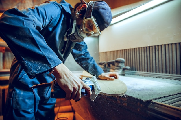 Stolarz za pomocą piły tarczowej do cięcia desek drewnianych. szczegóły konstrukcyjne pracownika płci męskiej lub poręczny mężczyzna z elektronarzędziami