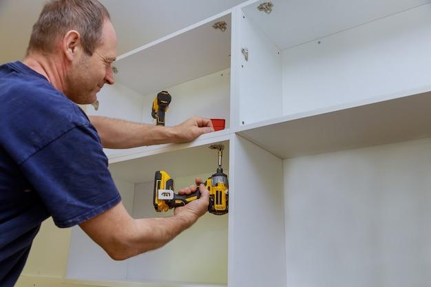 Stolarz zamontował metalowe zawiasy do szafek kuchennych do drzwi