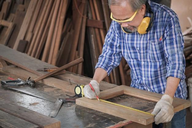 Stolarze wykonują pomiary drewna w stolarni.