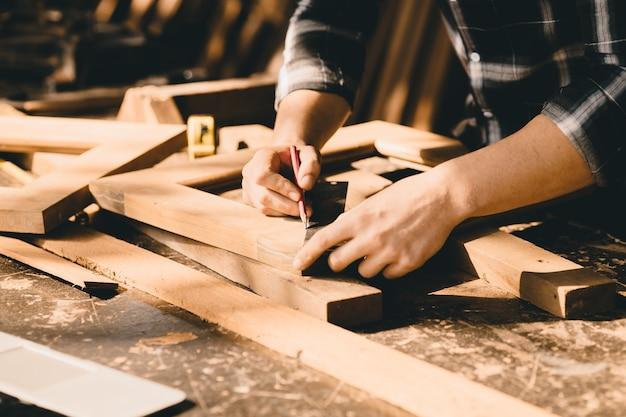 Stolarze z dużym doświadczeniem w produkcji mebli. master of woodcraft męskiej pracy z drewnianym kawałkiem rękodzieła z drobnymi szczegółami.