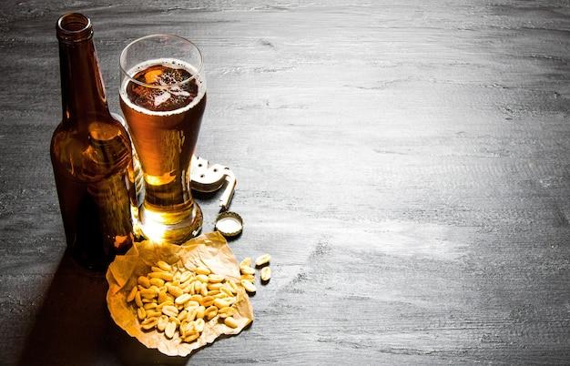 Stolik do piwa. piwo z orzeszkami ziemnymi na czarnym drewnianym stole. wolne miejsce na tekst.