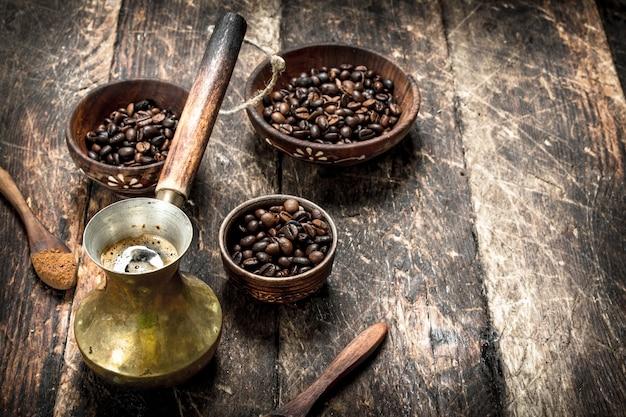 Stolik kawowy. świeżo parzona kawa z ziarnami w misce. na drewnianym stole.