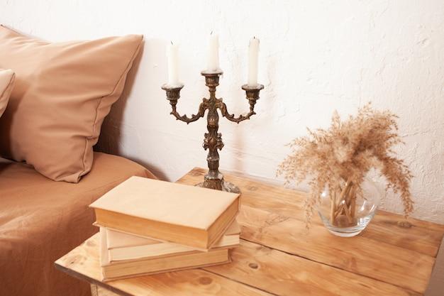 Stolik nocny z książkami, pampasami w szklanym wazonie i świecznikiem.