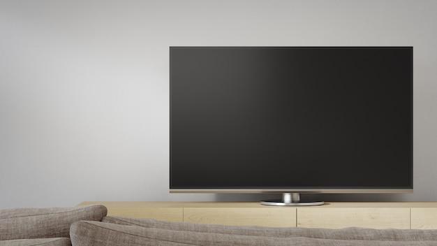 Stolik pod telewizor przy białej ścianie jasnego salonu i sofa na tle telewizora w nowoczesnym domu