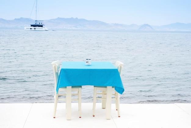 Stolik w kawiarni serwowany z niebieskim obrusem w pobliżu wybrzeża morskiego na relaksujące wakacje