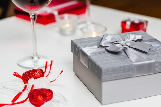Stolik z lampką wina i prezentami
