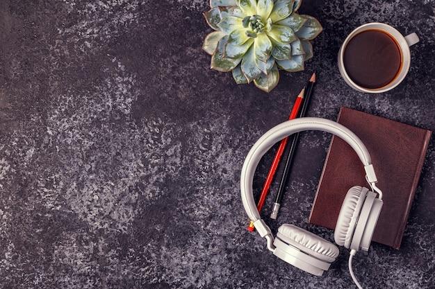 Stolik z notatnikiem, słuchawkami i kawą
