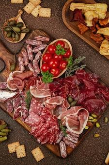 Stolik z różnymi przystawkami, serem, wędlinami, przekąskami i winem. kiełbasa, szynka, tapas, oliwki, ser i krakersy na przyjęcie w formie bufetu.