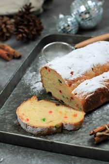 Stollen boże narodzenie. tradycyjny niemiecki chleb bochenek ze słodkimi owocami z cukrem pudrem. świąteczne nakrycie stołu, ozdobione choinką i dekoracją mini choinki. ścieśniać