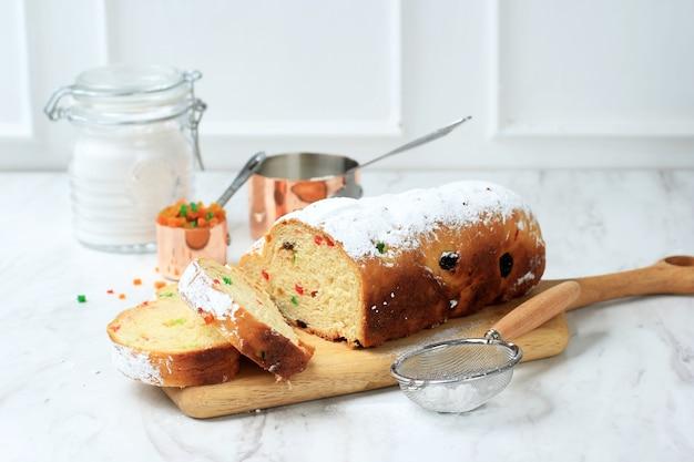 Stollen boże narodzenie. tradycyjny niemiecki chleb bochenek ze słodkimi owocami z cukrem pudrem. świąteczne nakrycie stołu, ozdobione choinką i dekoracją mini choinki.