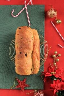 Stollen boże narodzenie. tradycyjny niemiecki chleb bochenek ze słodkimi owocami z cukrem pudrem. świąteczne nakrycie stołu, ozdobione choinką mini choinką i dekoracją.