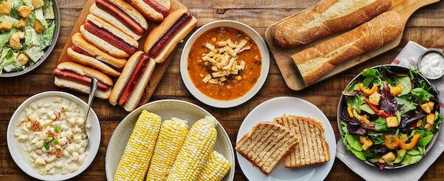 Stołowy posiłek z hot dogami, serem z grilla, zupą i sałatką w płaskiej kompozycji