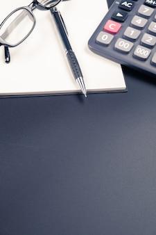 Stołowy widok pióro, notatnik i kalkulator na biurowym biurku ,.